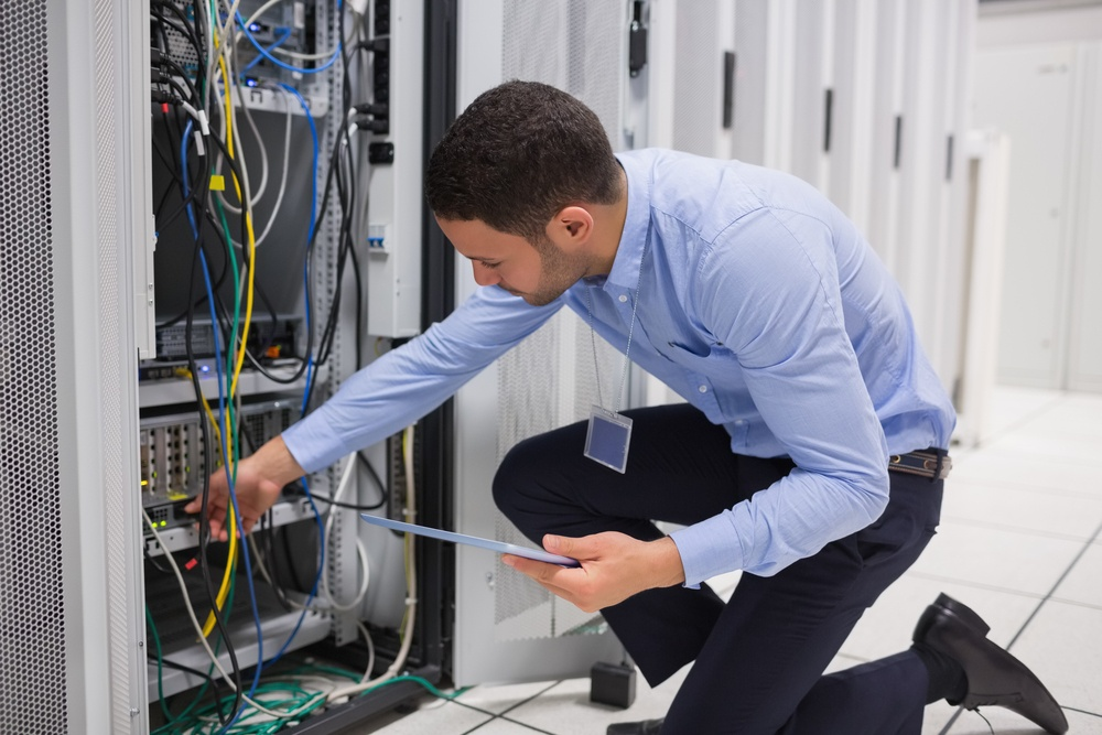 Man checking tablet pc as he is plugging cables into server in data center.jpeg